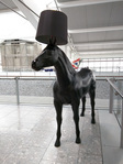 A horse wearing a lamp shade. Of course.